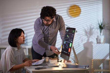 Jonge, bebaarde zakenman wijzend op computermonitor en praten met jonge zakenvrouw over financiële grafieken