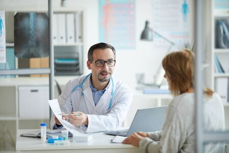 Mature healthcare worker showing some document to his patient and explaining the treatment for her while they sitting at office