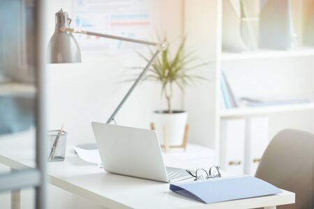 Close-up of workplace with laptop and folder on it at light modern office Stock Photo