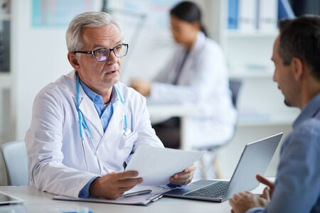 Senior doctor in eyeglasses and in white coat sitting at the table with document and explaining the treatment to his patient at office