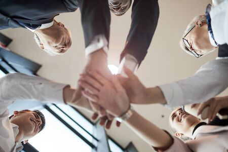 Low angle view of business team holding hands and cooperating with each other during team work at office