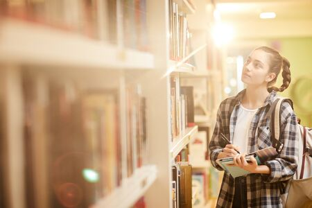 Young woman holding books and making a list of books for studying before the exam while standing near the bookcase at the library