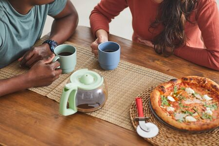 Close-up of young couple sitting at wooden table drinking coffee and eating pizza during lunch time