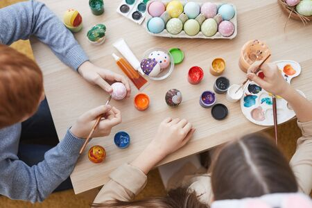 High angle view of two friends sitting together at the table and painting Easter eggs with paintbrushes Foto de archivo