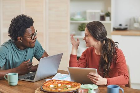 Young man and young woman sitting at the table with their gadgets and discussing work during lunch in the kitchen at home Stock Photo