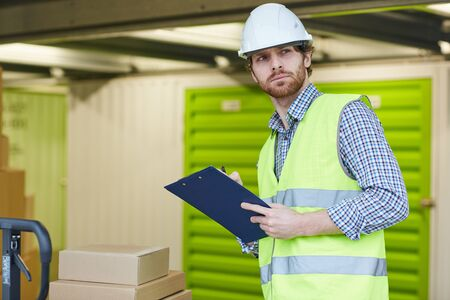 Serious manual worker in work helmet standing with clipboard and controlling the work in the storage