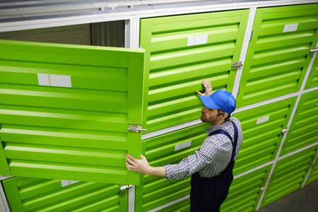 Young man in overalls and in cap opening the door of chamber while working in stockroom