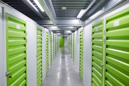 Image of empty corridor of storage room with green storage boxes
