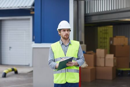 Young worker in working clothing holding clipboard and waiting for the delivery of cargo outdoors