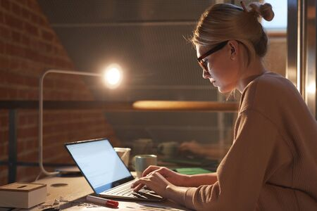 Young blonde woman in eyeglasses and in casual clothing sitting at desk and working on laptop till late at office Standard-Bild