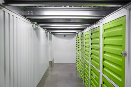Image of empty modern warehouse with green storage boxes