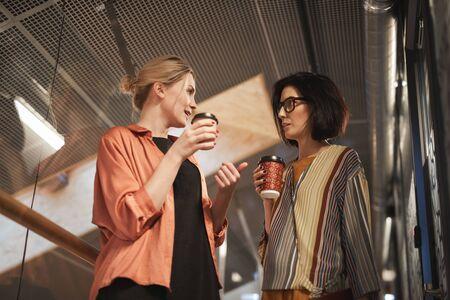 Twee zakenvrouwen die met elkaar praten en koffie drinken tijdens de koffiepauze op kantoor
