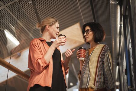 Two businesswomen talking to each other and drinking coffee during coffee break at office