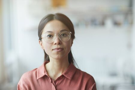 Portrait of serious young woman in eyeglasses looking at camera
