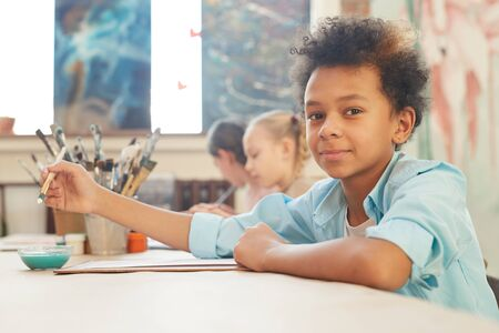Portrait of African boy looking at camera while sitting at the table and painting during art lesson Standard-Bild