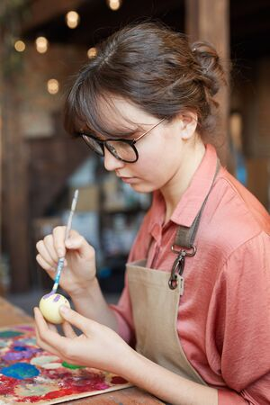 Young woman in eyeglasses sitting at the table and painting an Easter egg for Easter holiday