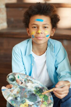 Portrait of African young boy holding palette with paints and looking at camera he painting at studio 写真素材