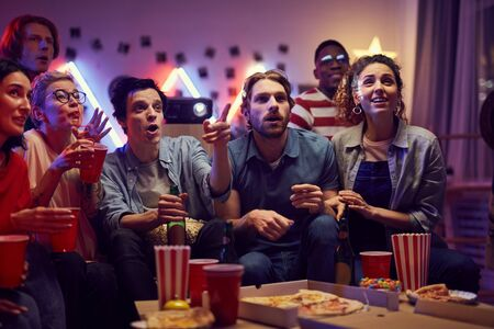 Group of young people sitting on sofa eating pizza and popcorn and watching a movie together during home party