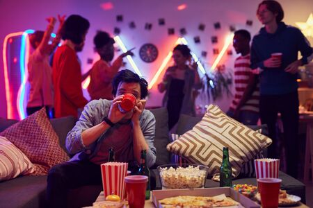 Young man sitting on sofa and drinking alcohol while his friends dancing in the background during a party