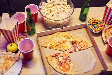 Close-up of pizza popcorn and alcohol drinks on the table at the party