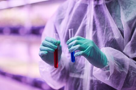 Close-up of chemist in protective gloves holding test tubes with different liquid in his hands