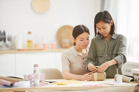 Young Asian woman and teen girl spending time together at hme preparing gifts for Mothers Day holiday, copy space