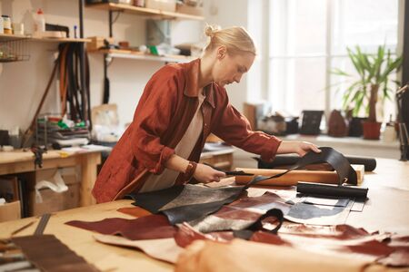 Young adult blond woman in casual outfit standing at table in her workshop cutting out leather for new craftwork