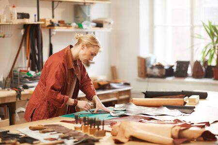 Horizontal side view portrait of modern female artisan doing leather craftwork standing at table in her workshop