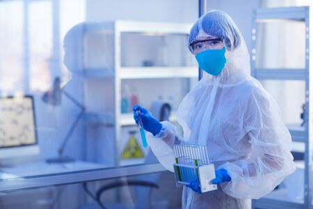 Unrecognizable female pharmacologist wearing disposable protective uniform holding test-tube with blue liquid looking at camera, horizontal medium shot
