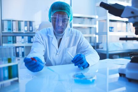Professional pharmacologist sitting at desk working on new medication in modern laboratory, horizontal portrait