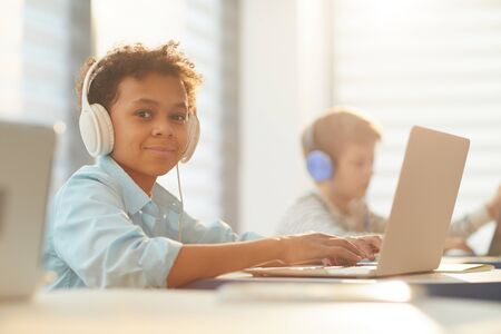 Medium portrait of African American boy wearing headphones using laptop while studying at school, copy space