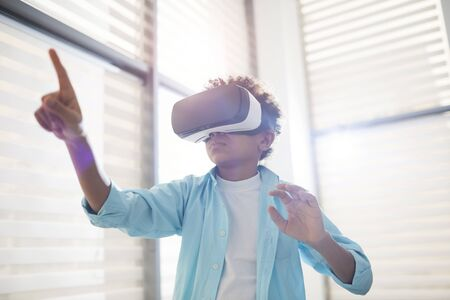Horizontal low angle shot of unrecognizable middle schooler using VR headset pointing finger at something, copy space
