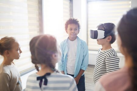 Middle school student testing VR glasses, his classmates standing around him waiting for their turn