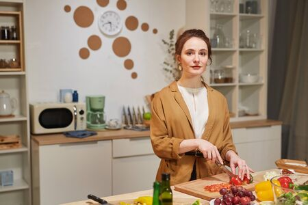 Portrait of young beautiful housewife looking at camera while cutting vegetables for salad in domestic kitchen Stock Photo