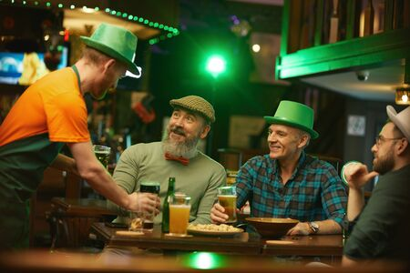 Group of men sitting at the table and talking to the waiter while he bringing glasses of beer for them in the pub
