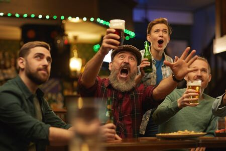 Excited people drinking beer and screaming they cheering for the football team in sport bar
