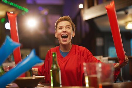 Young excited woman in red shirt cheering for football team in sport bar