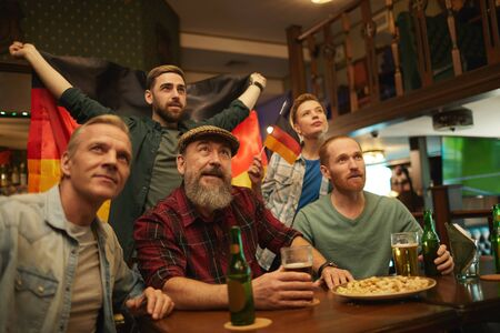 Group of German people sitting at the table drinking beer and cheering for their native football team in sport bar