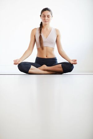Young beautiful woman in sports bra sitting in lotus position with her eyes closed and meditating isolated on white background Banco de Imagens