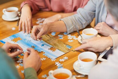 Close-up of family of four sitting at the table drinking tea and collecting puzzles together
