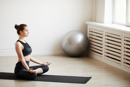 Young fit woman sitting on exercise mat and relaxing during meditation in health club
