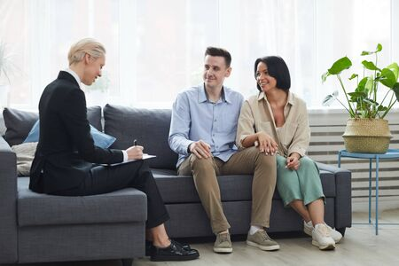 Mature businesswoman sitting on the sofa and concluding the contract with young couple they are going to buy a new house