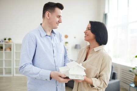Young couple holding model of the house and smiling to each other while standing in the living room at home