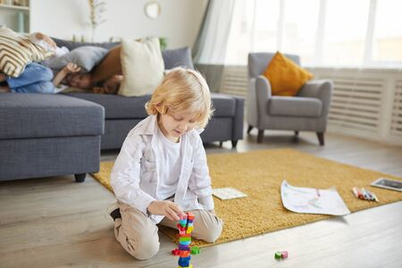 Little boy sitting on the floor and playing with colored blocks in the living room at home