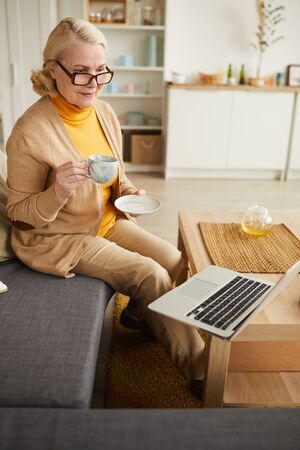 Senior woman in eyeglasses drinking tea and watching her favourite film on laptop she sitting on sofa in the living room