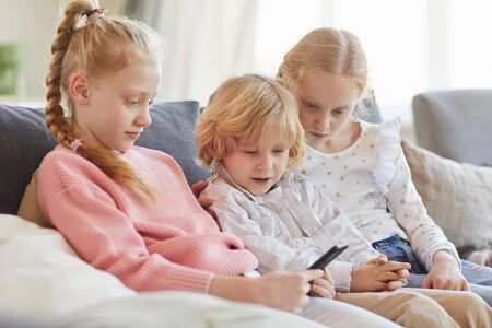 Group of children sitting on sofa and using mobile phone together during their leisure time at home