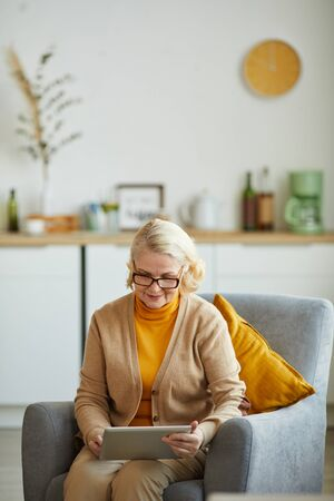 Mature woman in eyeglasses sitting n armchair and using digital tablet in the living room at home Stock Photo
