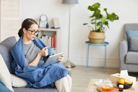 Young woman in eyeglasses sitting on sofa with digital tablet and drinking coffee in the living room at home