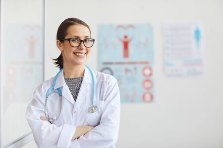 Smiling female doctor in eyeglasses and in white coat working at hospital she standing at her office