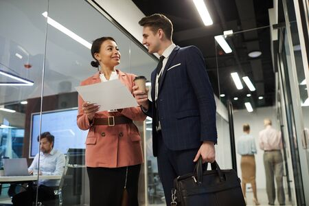 Young smiling businesswoman holding business contract and discussing it with businessman who standing with coffee drink and suitcase Banque d'images